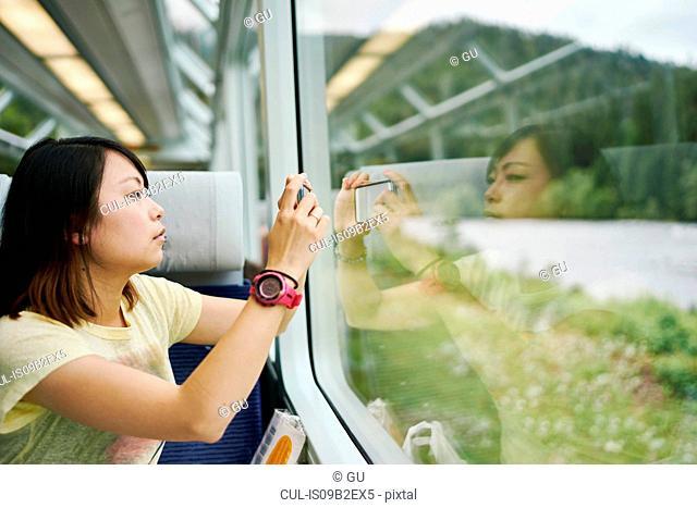 Female tourist photographing through passenger train window, Chur, Switzerland