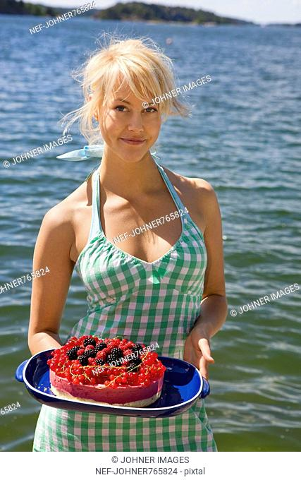 Young woman holding a cake with different berries, Sweden