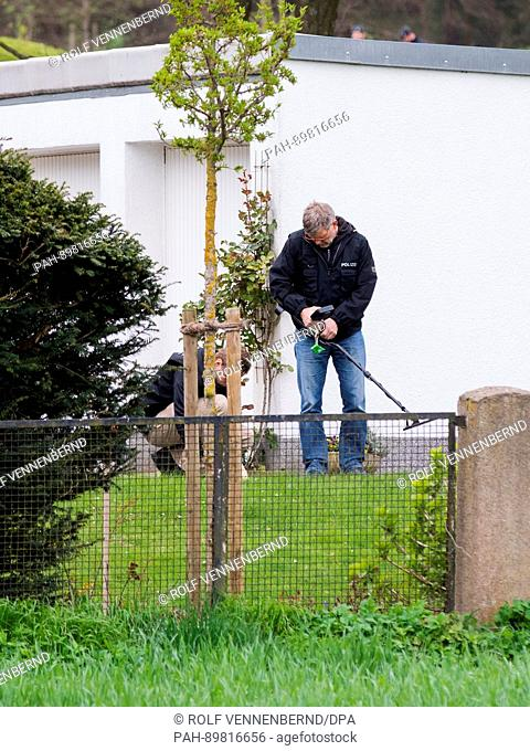 Investigators secure evidence with a metal detector on the private grounds to which the hedge in which the explosions occurred belongs next to the l'Arrivée...