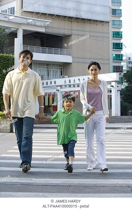 Family crossing crosswalk, holding hands