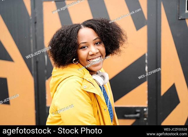Young woman smiling by door