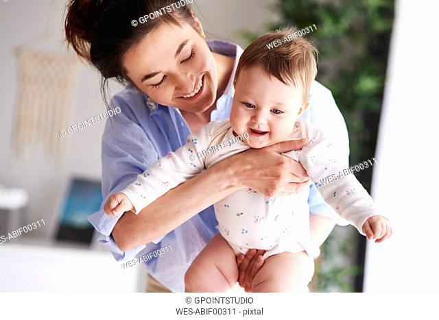 Happy mother carrying her baby at home