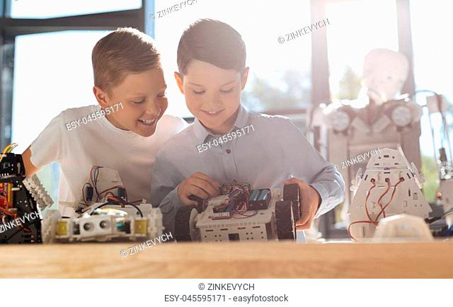 Curious look. Merry smiling little boy sitting at the table next to his friend constructing a robotic vehicle and looking at his work with curiosity