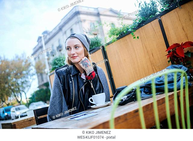 Young tattooed woman sitting in pavement cafe