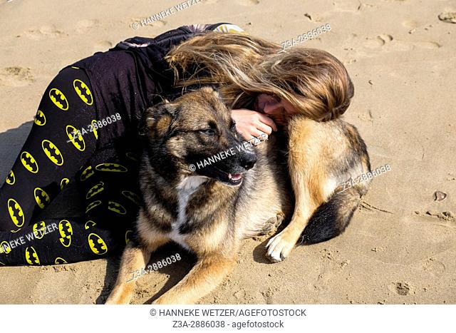 A girl and her dog sleeping at the beach of Scheveningen, The Hague, The Netherlands, Europe