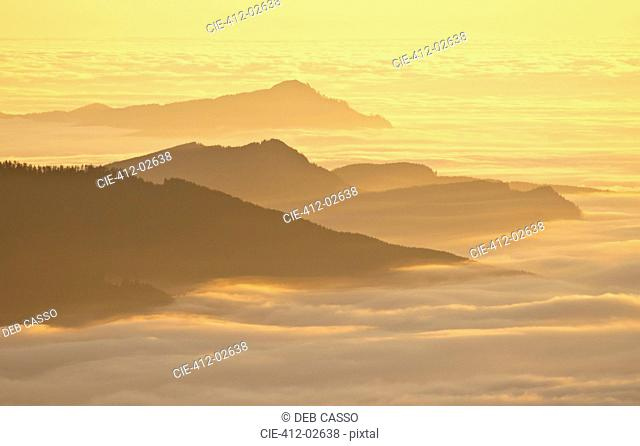 Aerial view of mountaintops over clouds at sunset