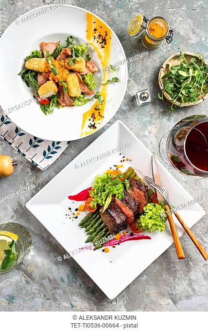 Dinners of roast beef and meat salad with red wine