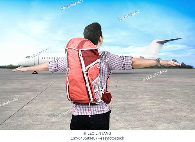 Happy asian traveler with backpack enjoying the trip by a plane