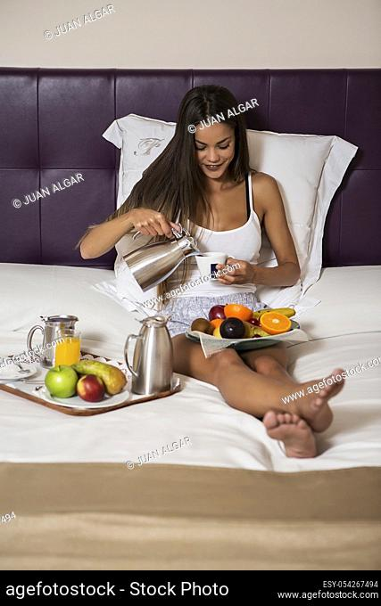 Charming woman pouring coffee in cup while sitting on bed with mixed fruit on plate