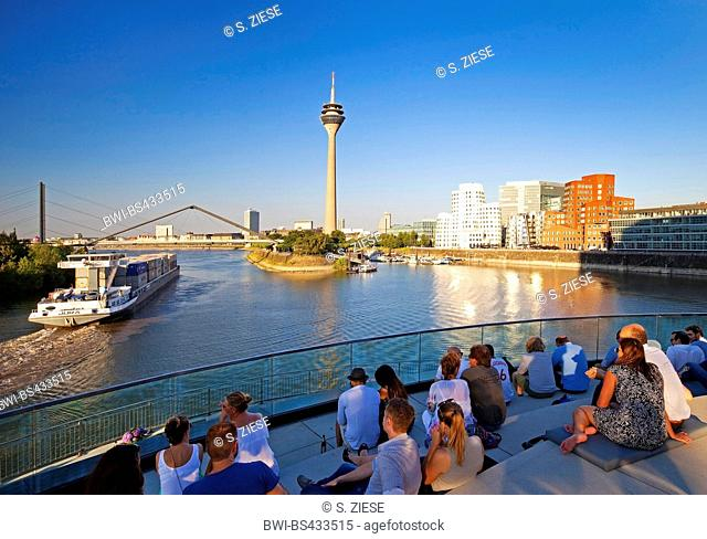 people on a restaurant terrace with view onto the Rhine tower, Germany, North Rhine-Westphalia, Duesseldorf