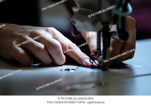 25 April 2019, Hessen, Weiterstadt: A prisoner is sewing at a workplace in the tailoring department of the Weiterstadt correctional facility