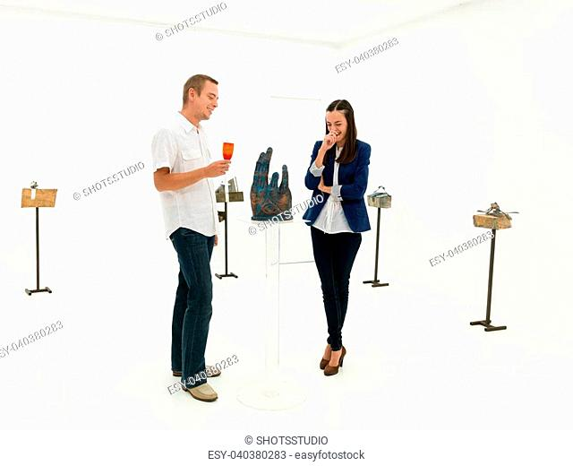 people standing in front of contemporary sculpture talking about it and laughing, in an art gallery