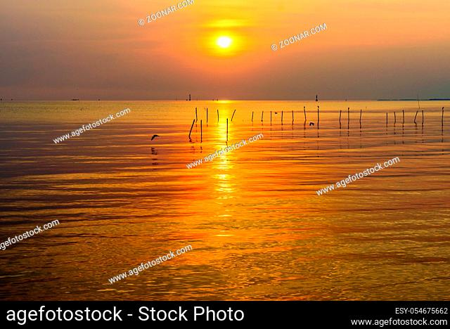 Beautiful nature landscape bright yellow sun reflecting orange light on the water surface of the sea and golden sunlight in sky