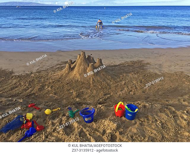 A man wades into the water while a castle and tools are strewn about on the sand, sand, Charley Young Beach, S. Kihei, Maui, Hawaii, USA