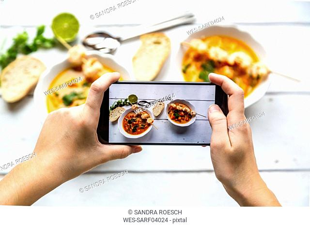 Girl taking photo of bowls with sweet potato soup with smartphone, close-up