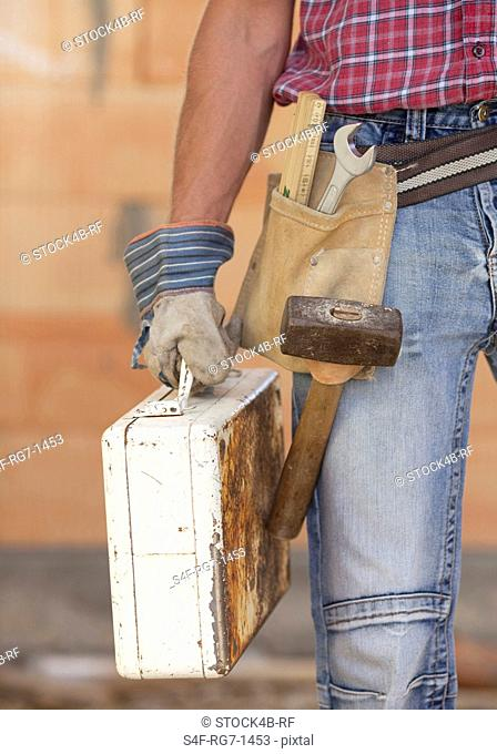 Builder with tool kit in front of brick wall
