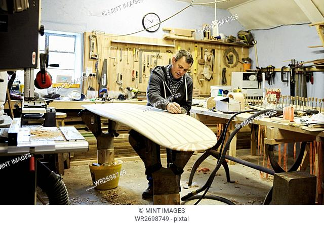 Man standing in a workshop sanding and shaping a wooden surfboard