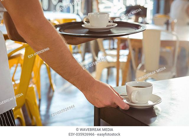 Cropped hand of waiter serving coffee