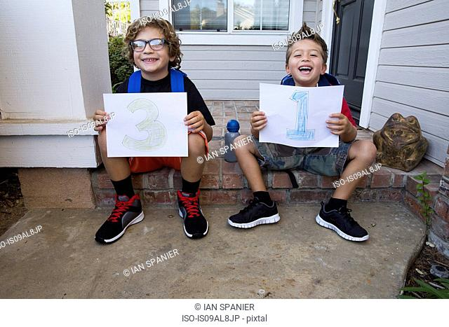 Portrait of two brothers sitting in porch holding up pieces of paper with 3 & 1