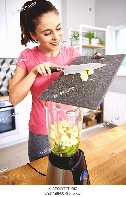 Smiling young woman preparing smoothie in the kitchen