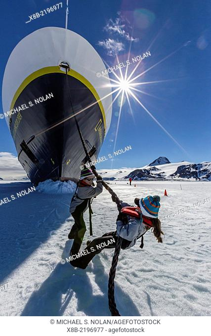 """Young girls """"""""hauling"""""""" the National Geographic Explorer on first year sea ice in Duse Bay, Erebus and Terror Gulf, Weddell Sea, Antarctica"""