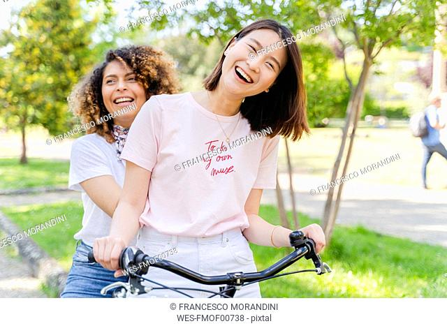 Two happy women on bicycle in park