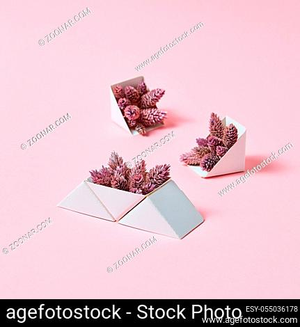 Creative composition of three cardboard boxes with cones on a pink background with space for text. Autumn layout