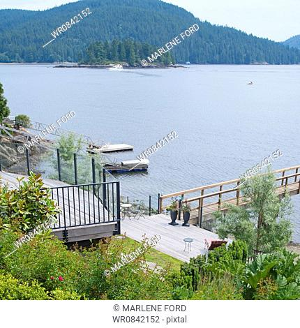 Deep Cove. View over the coastline and wooded hillside. Pine forests. Jetty and dock. Boats moored