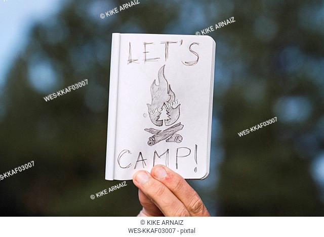 Hand in a forest holding 'Let's Camp' sign