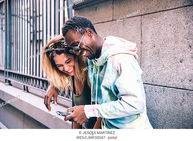 Laughing couple using cell phone outdoors