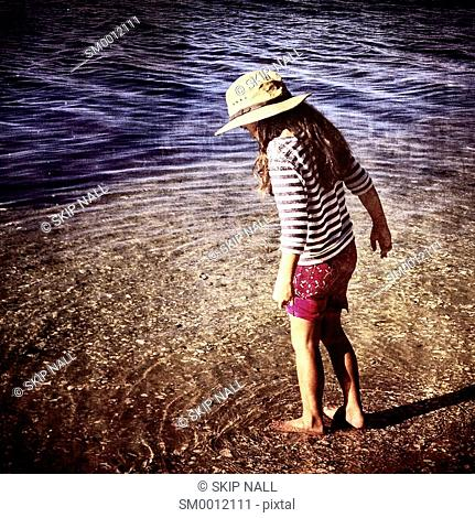 Little girl wading through the water at the beach