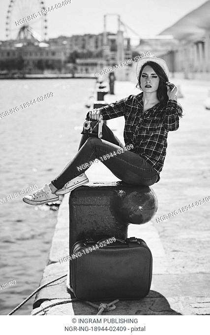 Young woman taking photographs with a vintage camera sitting in a harbour. Girl wearing plaid shirt, blue jeans and sun hat