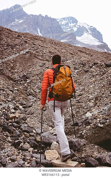 Male hiker with backpack walking on mountain