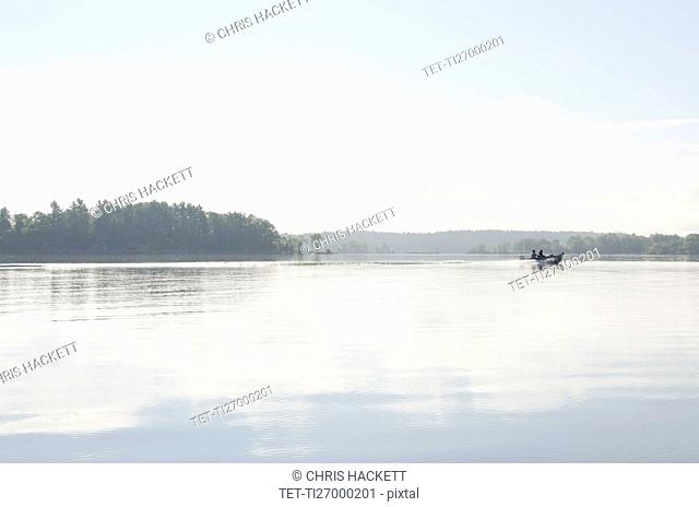 People traveling in boat on lake