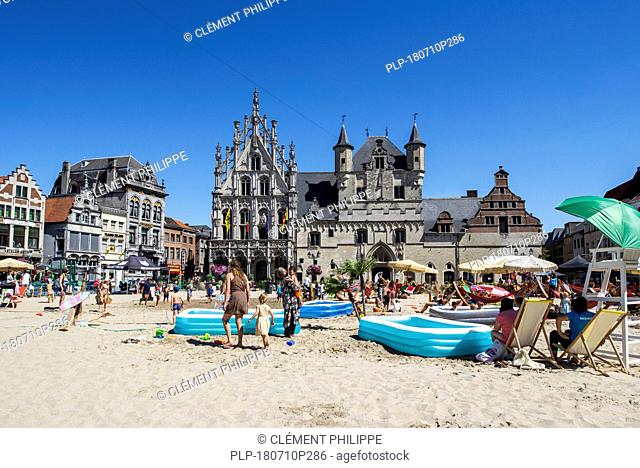 Sandy beach with playground for children on the Market Square / Grote Markt in the city Mechelen / Malines in summer, Antwerp, Flanders, Belgium