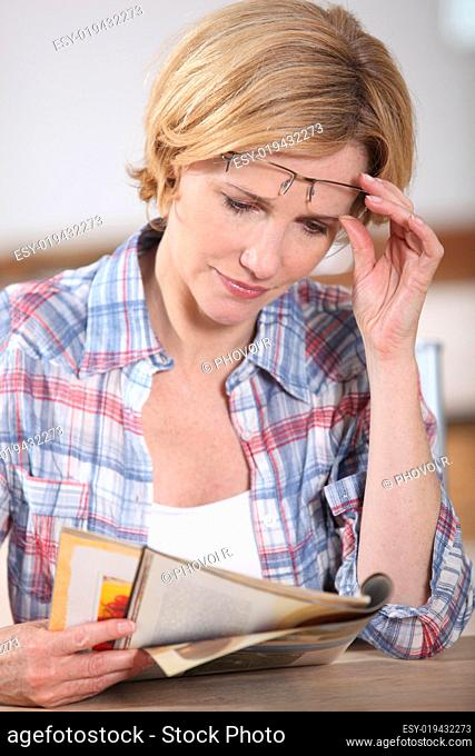 Woman raising her glasses to read something in a magazine