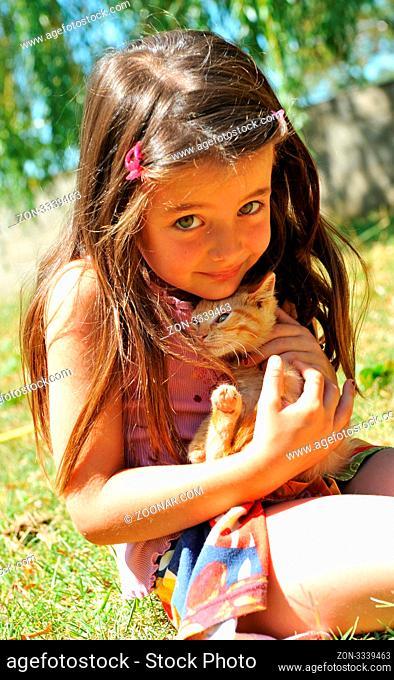 little girl and kitten in a garden