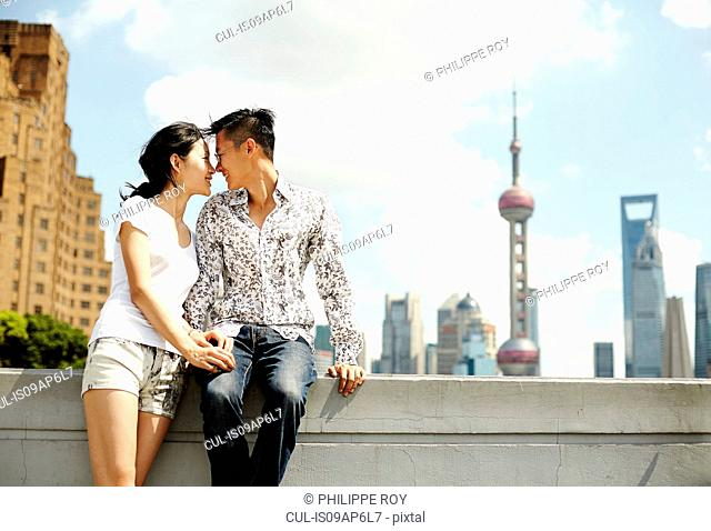 Romantic tourist couple sitting on wall, The Bund, Shanghai, China