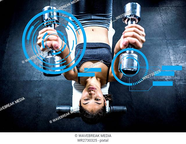 Fit woman exercising with dumbbells in gym