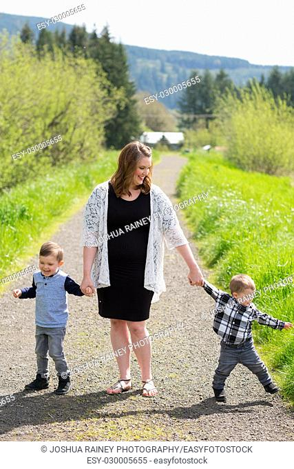 Realistic lifestyle portrait of a mother and her two sons in a field outdoors in Oregon