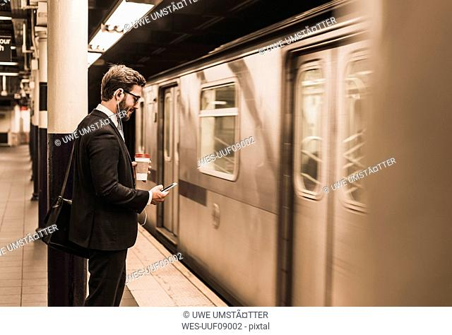 Young businessman waiting at metro station platform, using smart phone
