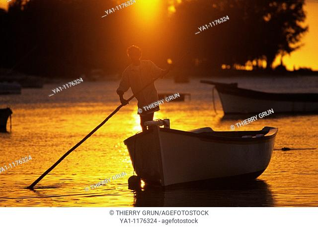 Local fisherman on his boat at sunset, Cape Malheureux, Mauritius Island, Indian Ocean