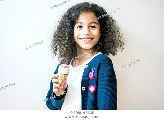 Cheeky little girl smiling at camera, eating ice cream