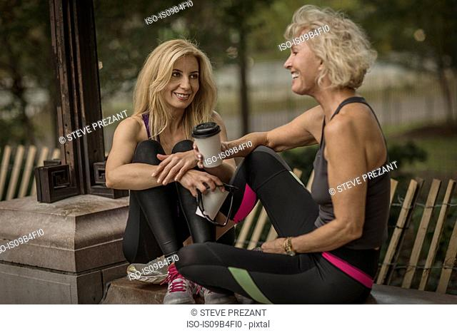 Two mature female friends training in park, sitting on wall with takeaway coffee
