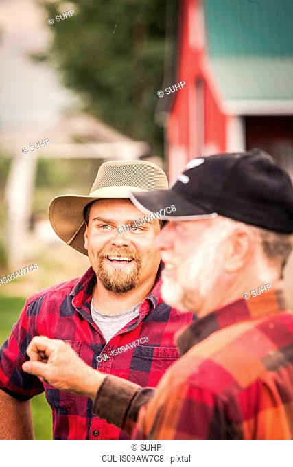 Farmers wearing plaid shirts chatting on farmland