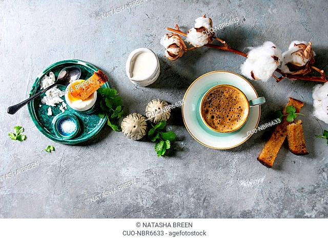 Breakfast with cup of coffee and soft boiled egg, served in green ceramic egg cup with salt, pepper and toasted bread, jug of cream and cotton flowers over grey...