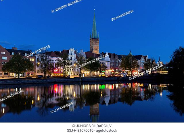 The church of St. Petri and historic houses mirrored the river Trave in Luebeck at dusk. Schleswig-Holstein, Germany