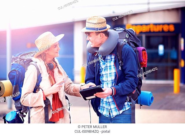 Backpacker couple using digital tablet at airport