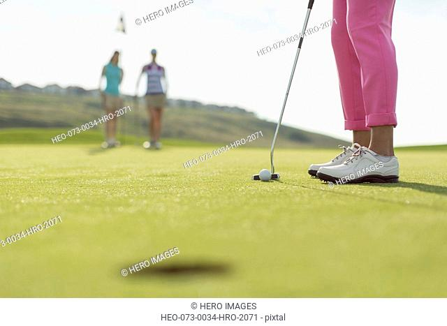 close-up of golf ball and putter with female golfers in the background