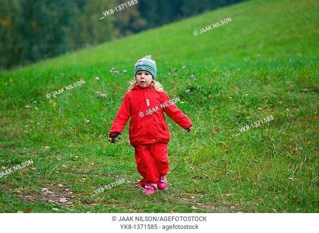 Two Years Old Girl Running in Hilly Green Meadow